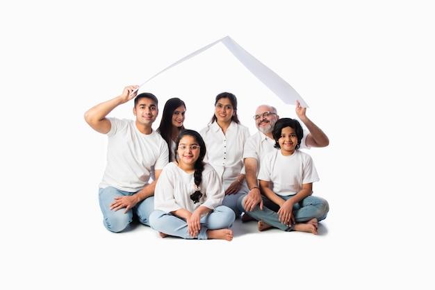 Famiglia indiana e concetto immobiliare - famiglia asiatica multigenerazionale che tiene in mano un modello di casa di carta con chiavi contro il muro bianco
