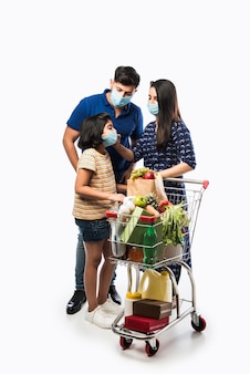 Indian family shopping con i bambini durante l'epidemia di virus. madre, padre e figlia che indossano una maschera chirurgica per l'acquisto di generi alimentari al supermercato. famiglia in negozio.