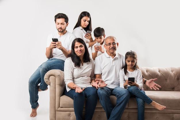Famiglia indiana seduta sul divano mentre gli anziani si annoiano e i giovani sono impegnati sullo smartphone