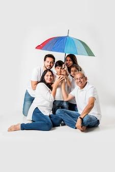 Famiglia indiana seduta con ombrello su sfondo bianco. messa a fuoco selettiva