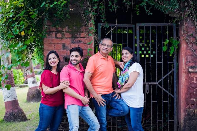 Famiglia indiana in fila contro il muro ricoperto di rampicanti. multi generazione di famiglie asiatiche nel parco o in giardino che si divertono, sano concetto di vita familiare