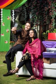Famiglia indiana che scatta una foto selfie utilizzando lo smartphone mentre indossa i tradizionali panni del festival il diwali o la cerimonia di matrimonio e si siede sul divano o sul divano