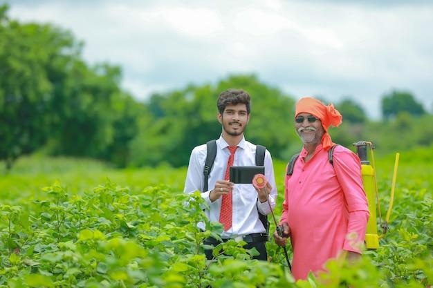 Agricoltore indiano discutendo con agronomo in fattoria e raccogliendo alcune informazioni