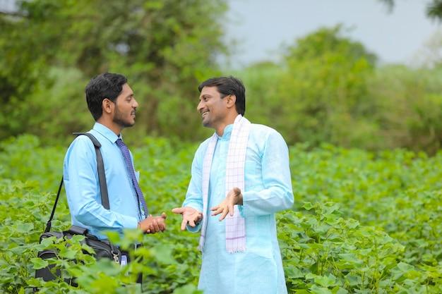 Contadino indiano discutere con l'agronomo presso farm e raccogliere alcune informazioni