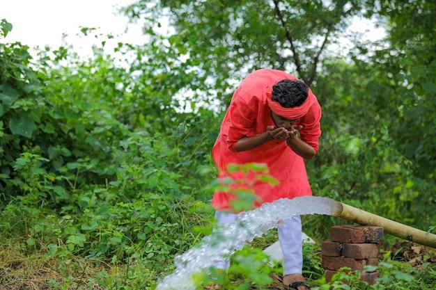 Acqua potabile dell'agricoltore indiano con la mano dalla conduttura al campo