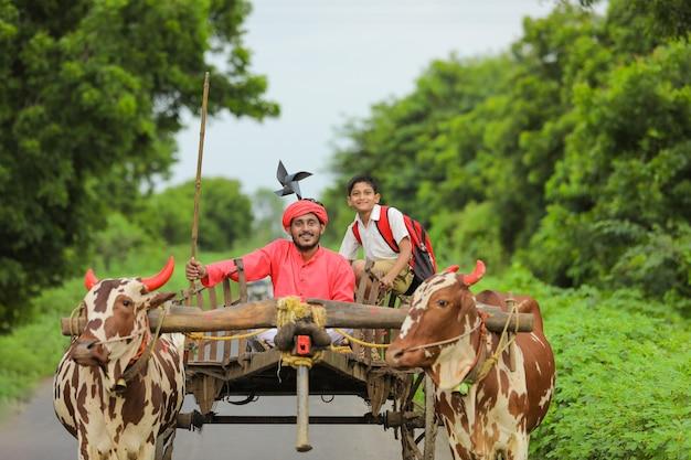 Agricoltore indiano e suo figlio sul carrello di buoi