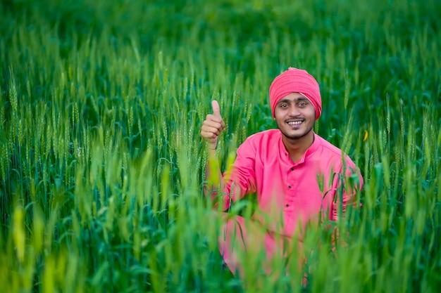 Coltivatore indiano che tiene pianta del raccolto in mano al campo di grano