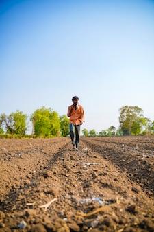 L'agricoltore indiano o il lavoro il tubo di irrigazione a goccia si assembla nel campo agricolo. scena rurale.