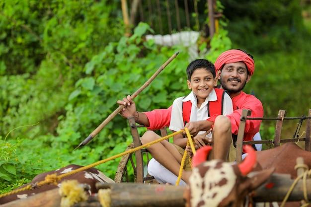 Agricoltore indiano e bambino in età scolare sul carrello di buoi
