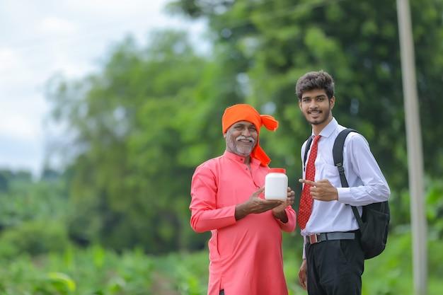 Agricoltore indiano che mostra la bottiglia del prodotto agro con agronomo