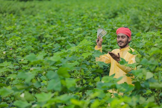 Coltivatore indiano che mostra soldi al campo di cotone
