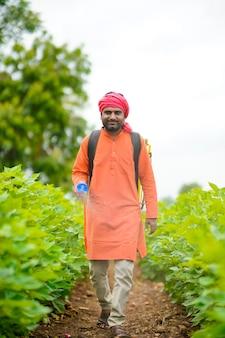 Contadino indiano che spruzza pesticidi sul campo di cotone.