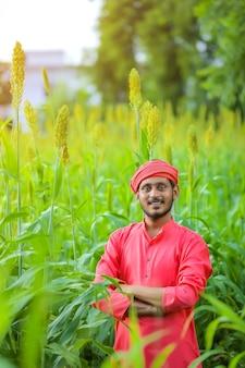 Coltivatore indiano in piedi in un campo di sorgo