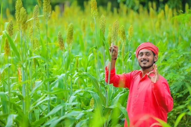 Coltivatore indiano in piedi nel campo di sorgo