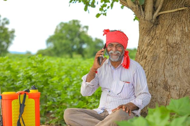 Coltivatore indiano che parla sul telefono cellulare al campo agricolo