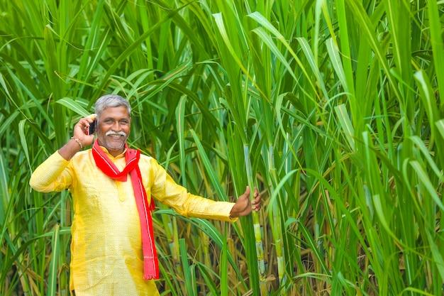 L'agricoltore indiano parlando al telefono cellulare al campo agricolo