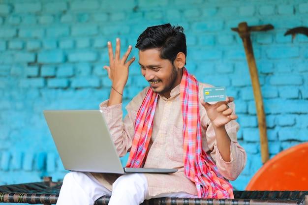 Contadino indiano che utilizza laptop e carta a casa.