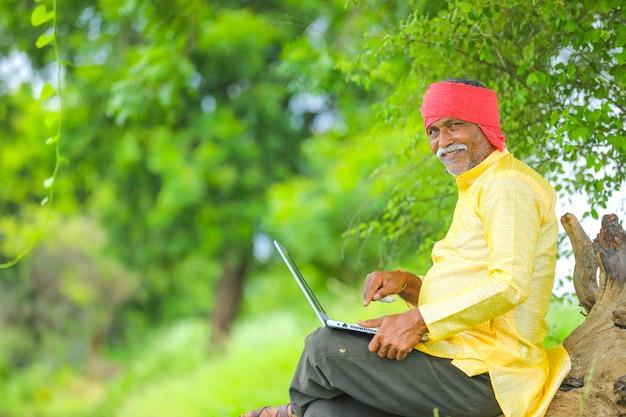 Coltivatore indiano che utilizza computer portatile al campo