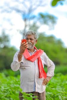 Agricoltore indiano utilizzando il telefono cellulare al campo di agricoltura