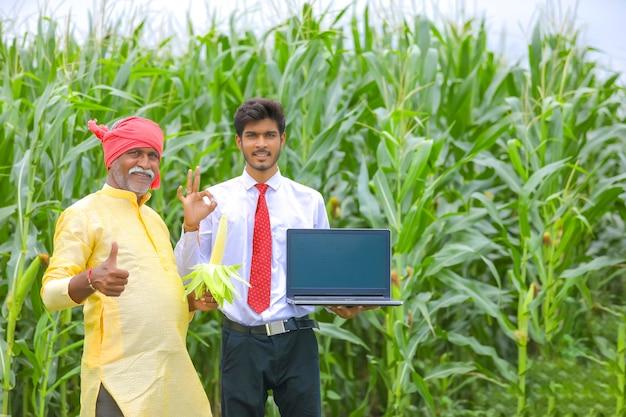 Contadino indiano con agronomo al campo di mais e mostrando lo schermo del laptop