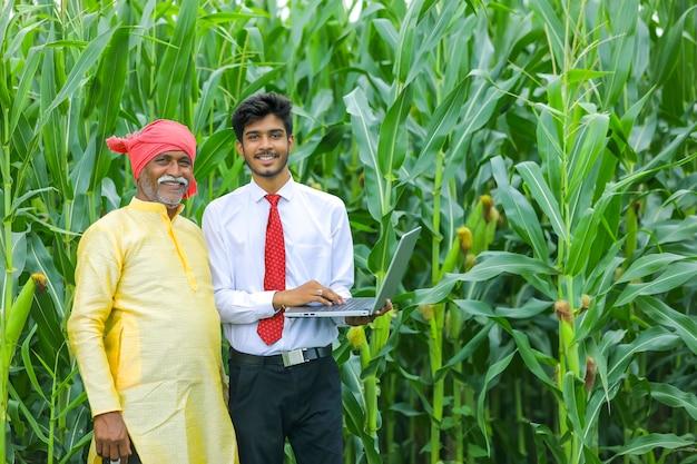 Contadino indiano con agronomo al campo di mais e mostrando alcune informazioni sul laptop