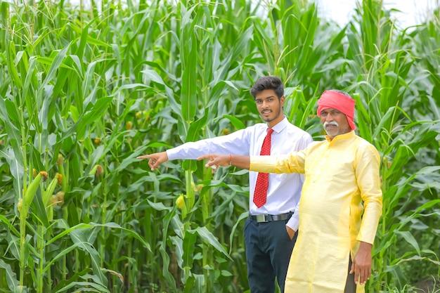 Contadino indiano con agronomo al campo di mais