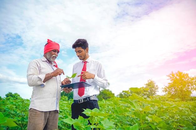 Contadino indiano con agronomo al campo di cotone, che mostra alcune informazioni sulla scheda