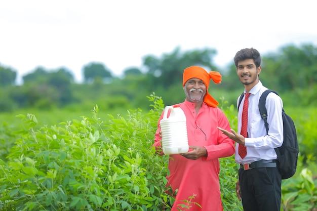 Contadino indiano con agronomo al campo, agricoltore e agronomo che mostra botle di fertilizzante