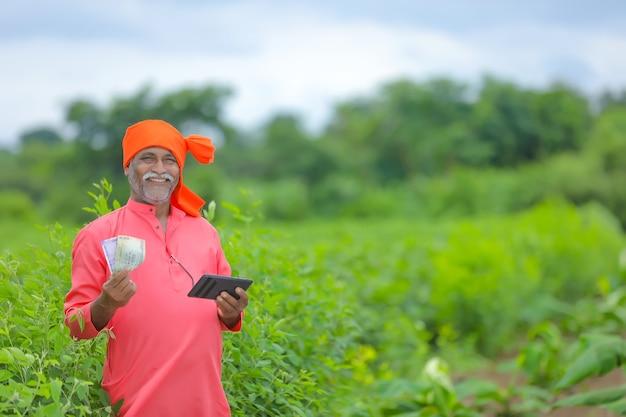 Coltivatore indiano con soldi e tablet