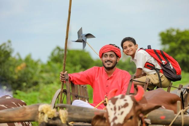 Contadino indiano con uno scolaro in un carro trainato da buoi
