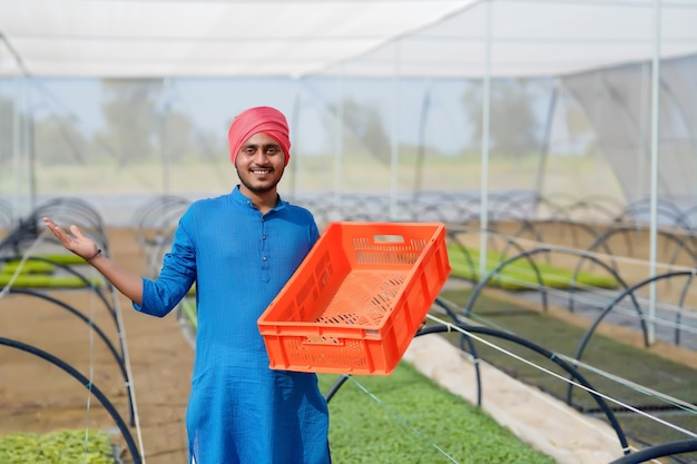 Coltivatore indiano che lavora alla serra