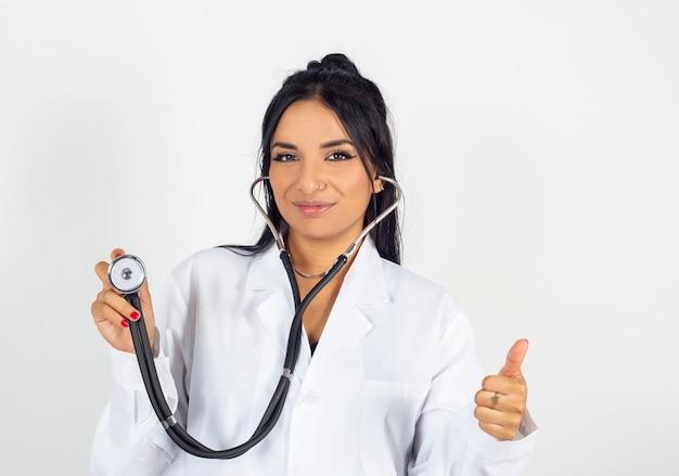 Medico femminile indiano in camice bianco con lo stetoscopio.