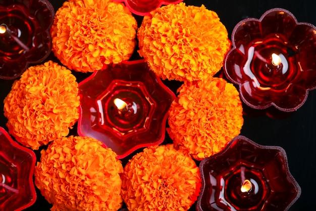 Festival indiano diwali, fiori di calendula e lampade a olio colorate su sfondo nero