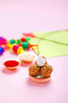 Concetto di festival indiano makar sankranti, aquilone colorato, corda e palla di semi di sesamo dolce.