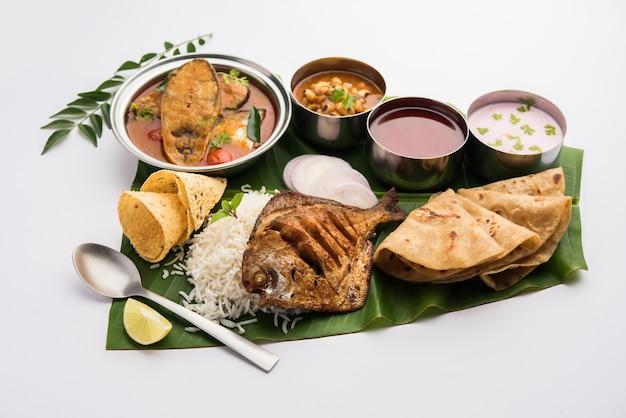 Piatto di pesce indiano e salse servite su foglie di banana
