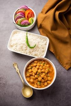 Cibo indiano chole chawal o curry piccante di ceci con riso semplice servito con insalata verde. messa a fuoco selettiva