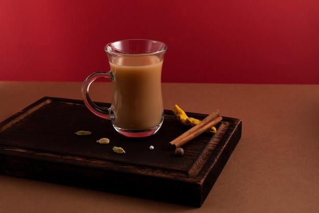 Tè allo zenzero indiano con latte e spezie sul rosso