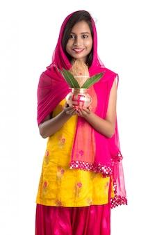 Ragazza indiana con in mano un tradizionale kalash in rame, festival indiano, kalash in rame con cocco e foglie di mango con decorazioni floreali, essenziali nella pooja indù.
