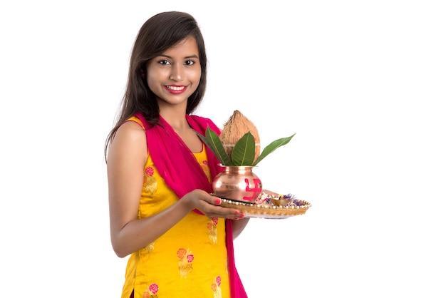 Ragazza indiana con un tradizionale kalash in rame con pooja thali