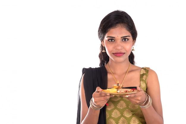 Indian girl esecuzione di culto, ritratto di una giovane e bella donna con pooja thali isolato su uno spazio bianco.