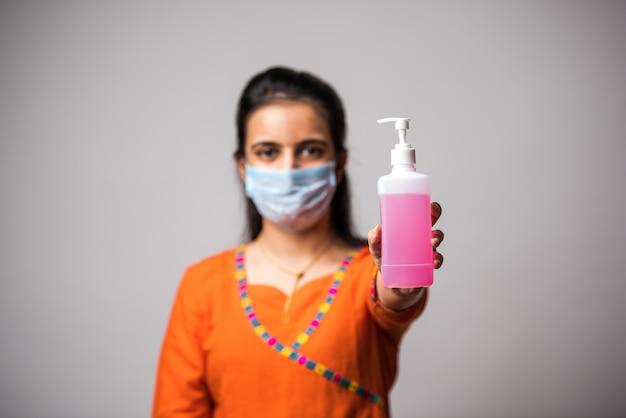 Ragazza indiana che mostra disinfettante per le mani indossando maschera medica. lavare le mani antisettico. concetto di corona virus