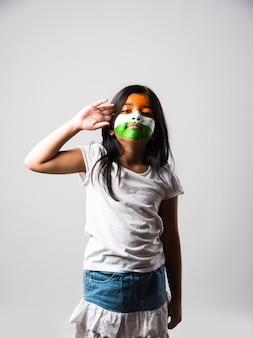 Ragazza indiana con giocattolo mulino a vento di carta composto da tricolore e faccia dipinta con i colori della bandiera indiana. adatto per il felice giorno dell'indipendenza o il saluto della festa della repubblica.