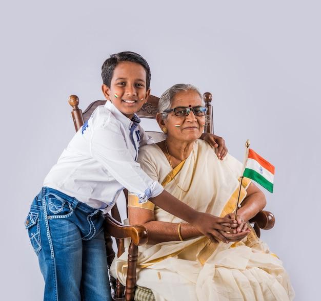 Nonna indiana e bambini che celebrano il giorno repubblicano o il giorno dell'indipendenza con facce dipinte con tricolore mentre si tiene la bandiera nazionale, isolato su sfondo bianco