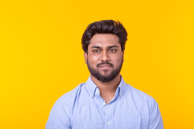 Uomo bello indiano che indossa camicia blu sulla parete gialla