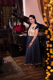 Marito indiano che suona il pianoforte per moglie. donne felici che si godono la musica suonata dal marito al pianoforte a coda