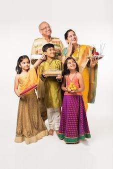 Bambini indiani con i nonni in abiti tradizionali che tengono regali, dolci e puja o pooja thali o si fanno selfie, isolati su sfondo bianco