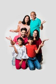 Bambini indiani con genitori e nonni, seduti isolati su sfondo bianco, foto in studio