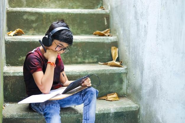 Ragazzino indiano che studia online utilizzando il telefono cellulare a casa