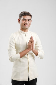 Uomo indiano nell'usura etnica e nei gesti benvenuti isolati su bianco