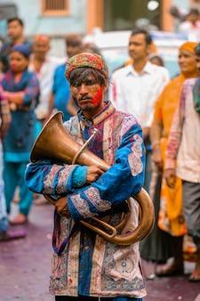 Uomo indiano che tiene la cornetta al festival di holi